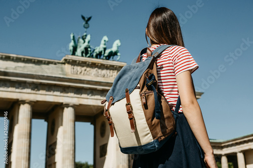 Photo  A tourist or a student with a backpack near the Brandenburg Gate in Berlin in Germany, looks at the sights