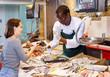 Salesman offering girl fresh mussels
