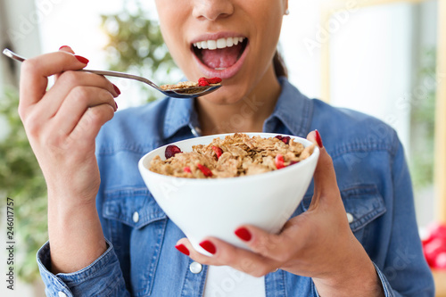 Fotografiet Smiling young woman eating breakfast cereals of bowl at home.