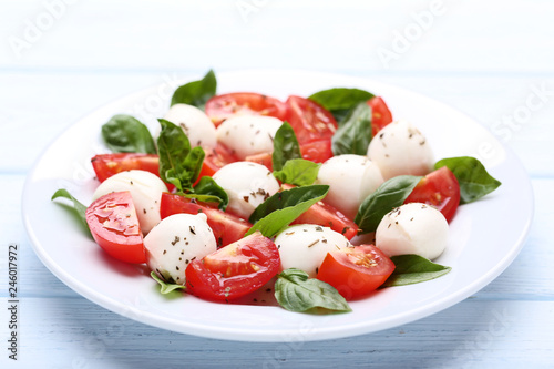 Fototapeta Mozzarella, tomatoes and basil leafs in plate on wooden table