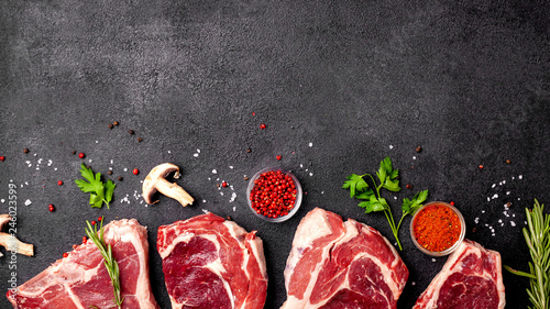 Meat raw steaks lie on a black background with vegetables, tomatoes, marasmade, mushrooms Canvas Print
