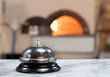 Pizzeria service bell close up wood fire oven in background