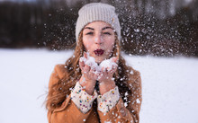 Young Woman Is Blowing Snow In Winter Park