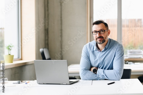 Photographie  Middle aged handsome man in shirt working on laptop computer in office