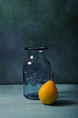 Still life with blue glass vase and fruits on turquoise background