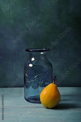 Fototapeta Still life with blue glass vase and fruits on turquoise background obraz