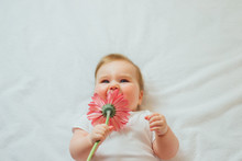 Beautiful Baby Holding A Flower On White Background
