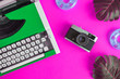 canvas print picture - Flat lay of typewriter with retro camera and inflatable floats with monstera leaves abstract on rose.