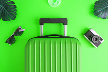 Luggage With Summer Vacation Accessories On Green.