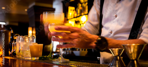 Photo Stands Cocktail Bartender with cocktails at a busy bar with motion blur. Bartender handing drinks to server with movement blur.