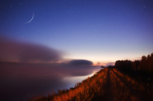 Waxing Crescent Moon Above Misty River Scenery.