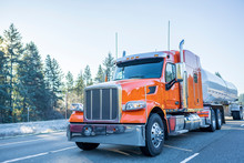 Big Rig Orange Classic American Semi Truck Transporting Liquid Cargo In Tank Semi Trailer Moving On The Winter Frosty Road