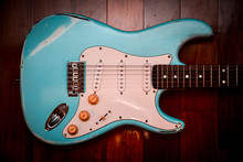 Light Blue Electric Guitar In A Brown Wood Background