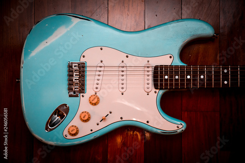 Photo  Light blue electric guitar in a brown wood background