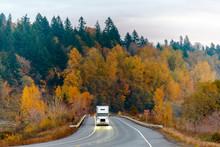 White Big Rig Semi Truck Transporting Goods On The Winding Autumn Wet Raining Road At Twilight