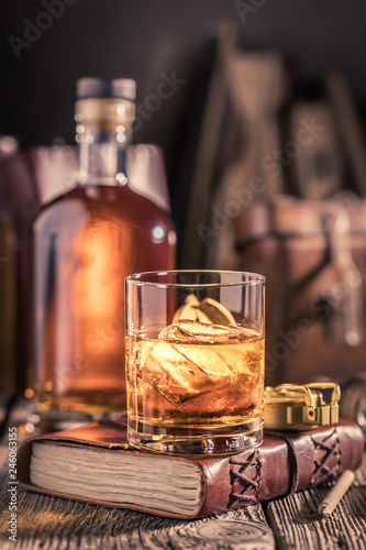 Glass of whisky with ice and golden bottle