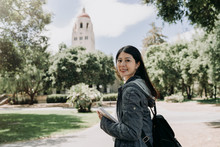 Female College Student Join Short Term Summer Tour Program To Learn Language Well In University. Young Girl Study Abroad In Stanford. Asian Woman Face Camera Smiling Holding School Book Go To Class