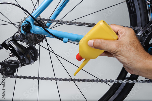 Mechanic oiling bicycle chain and gear with oil Canvas Print