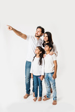 Father Pointing Finger While Standing With Wife And Kids Over White Background. Selective Focus