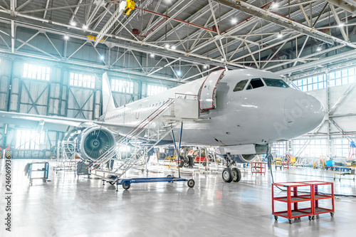 Fototapeta Aircraft under maintenance, checking mechanical systems for flight operations. Plane in the hangar obraz