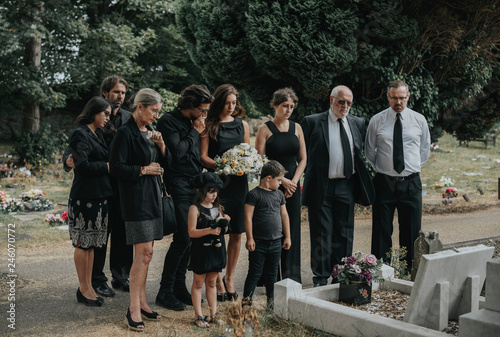 Family giving their last goodbyes at the cemetery Wallpaper Mural