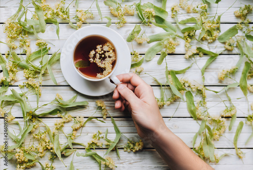 Female hand reaches for a cup of tea from linden flowers. The concept of herbal medicine. Treatment of cold and flu.