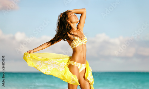 Sexy bikini body woman feeling free with slim stomach and smooth thighs wearing yellow fashion scarf skirt swimwear beachwear showing off weight loss Poster Mural XXL
