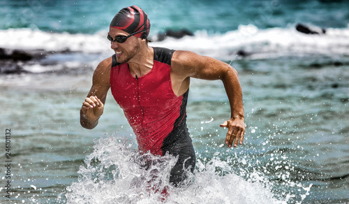 Triathlon swimming man running out of water during ironman race. Male triathlete finishing swim time competition. Fit athlete swimmer sprinting determined out of water in professional tri suit.