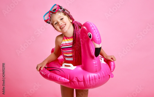 happy child girl in swimsuit with swimming ring flamingo on colored pink background - 246102918
