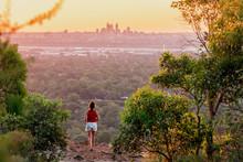 Girl Watches Sunset Over The Perth City Skyline From The Perth Hills (Kalamunda Zig Zag). Perth, Western Australia, Australia.