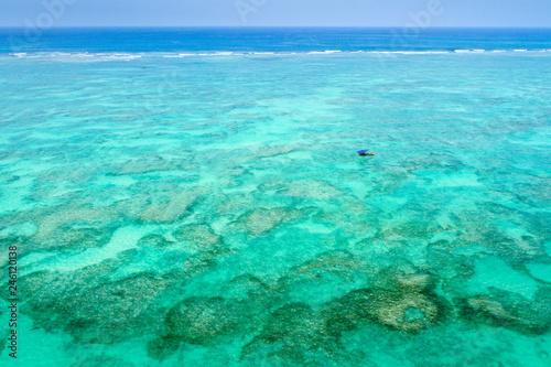 sail boat in green lagoon infant of reef on Zanzibar