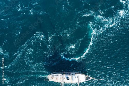 大きく波打つ海を一隻の船が走る風景
