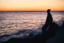 Silhouette Of A Slim Young Man Leaning On A Stone On The Coast And Looking At The Sea Surface On A Warm Summer Evening. Romantic Holiday Concept. Copyspace