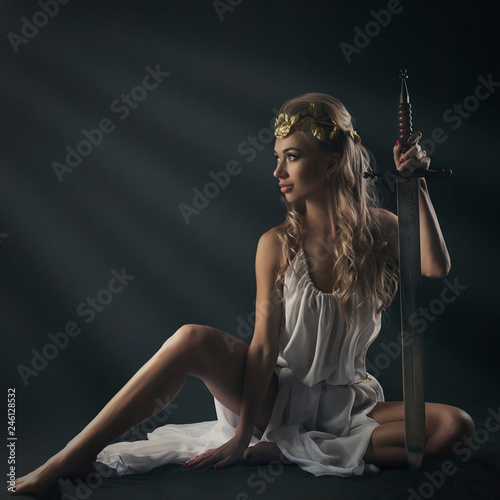 goddess young woman on darkt bg  with sword studio shot Fototapet