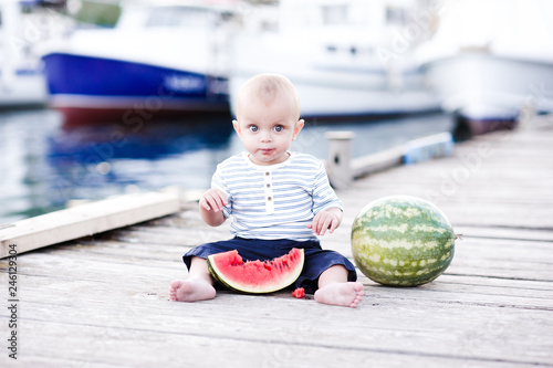 Foto  Cute baby boy eating watermelon outdoors. Summer season.