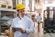 Close up of Caucasian hard working man holding tablet and looking away while standing in the storage. In background worker and forklift.