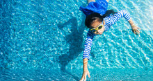 Little Girl Touch The Board Of A Swimming Pool To Finish The Swimming.Girl Swimming And Diving In Blue Pool With Swimwear.Child Learns To Swim Or Healthy Lifestyle Concept.