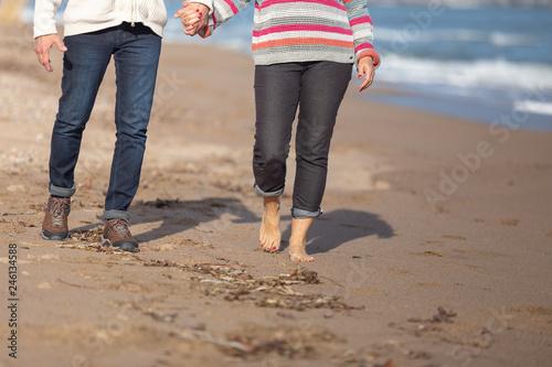 Fotografia  legs of couple walking on the beach