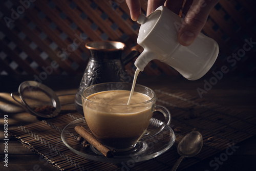 Tuinposter Chocolade Cup of black coffee on the table with cream