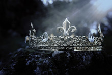 Mysterious And Magical Photo Of Gold King Crown Over The Stone Covered With Moss In The England Woods Or Field Landscape With Light Flare. Medieval Period Concept.