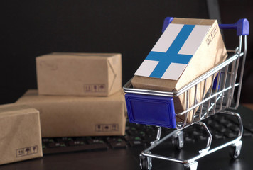 Parcel Boxes with a flag of Finland in a shopping cart on a laptop keyboard. Online shopping