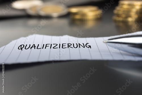 Qualifizierung auf einem Zettel mit Stift vor Geldmünzen Canvas Print