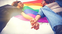 Beautiful Female Young Lesbian Couple In Love Holding Hands, And A Rainbow Flag, A Symbol Of The LGBT Community, Equal Rights, Beauty And Love
