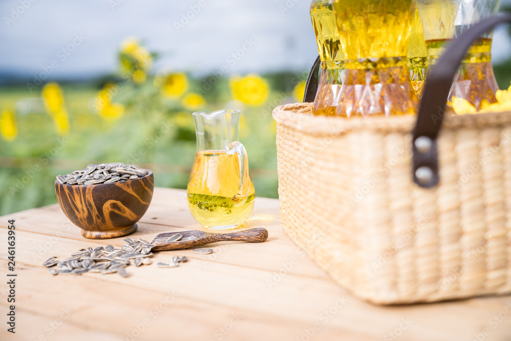 Fototapety, obrazy: Sunflower oil and seed on the wooden table in the sunflower fields