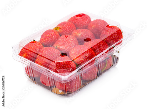 Ripe strawberries from the garden are packed in plastic boxes. Isolated on white background