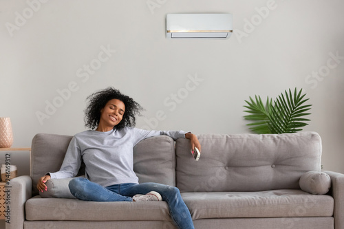 Fényképezés  Calm African American woman sit on couch relaxing under air conditioner at home,
