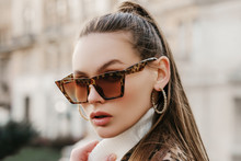 Outdoor Close Up Fashion Portrait Of Young Beautiful Fashionable Woman Wearing Stylish Animal, Leopard Print Sunglasses, Hoop Earrings, Turtleneck, Posing In Street Of European City. Copy, Empty Space