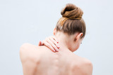 Young woman having pain in the back and neck. Health-care Concept. - 246172129