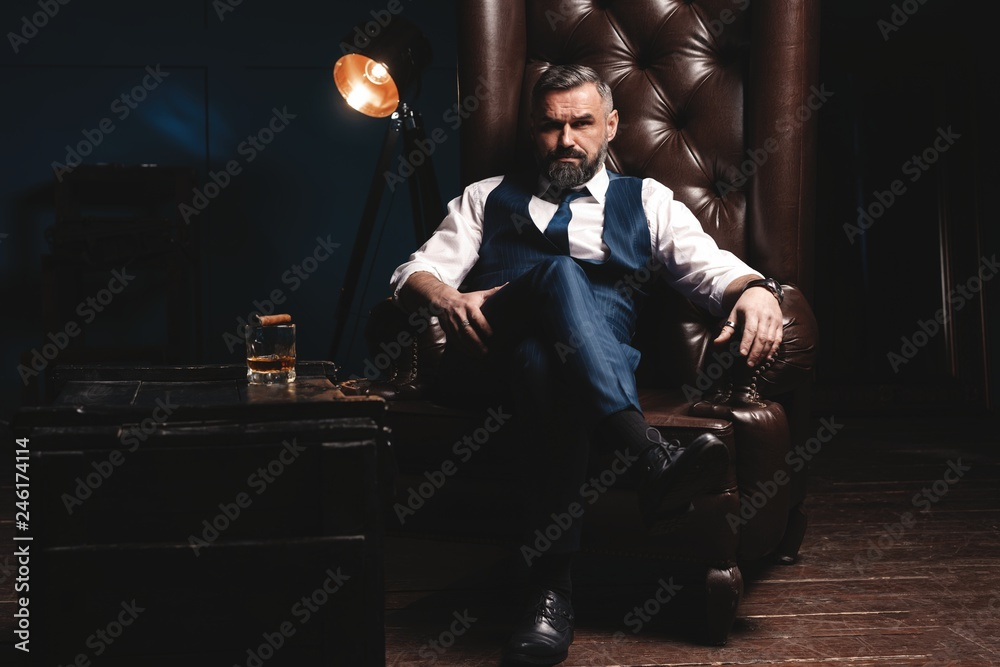 Fototapeta Attractive man with cigar and a glass whiskey