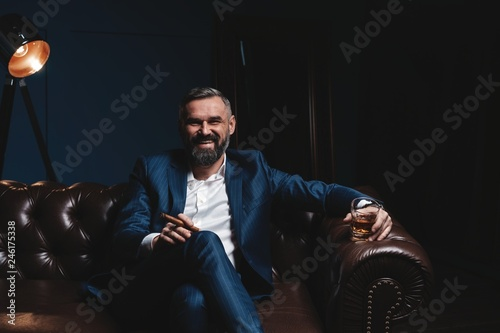 Fototapeta Attractive man with cigar and a glass whiskey obraz